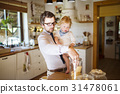 Young father at home with his little son eating 31478061