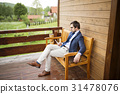 Businessman with smart phone sitting on front 31478076