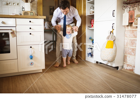 Young businessman holding hands of his son taking 31478077