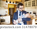 Businessman at home holding baby daughter in the 31478079