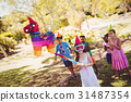 Little girl is going to broke the pinata for their birthday 31487354