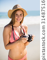 Attractive woman in bikini checking photographs 31487516