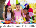 Portrait of cute girls preparing to blow on candle during a birthday party 31487887
