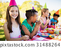 Close up of cute girl smiling in front of other children during a birthday party 31488264