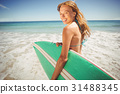 Woman holding surfboard on beach 31488345