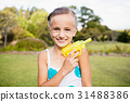 Kid posing at camera during a sunny day with her water gun 31488386