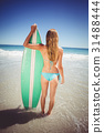 Woman standing with surfboard on beach 31488444