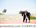 Businessman with laptop ready to run 31489018