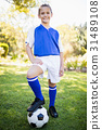 Front view of girl wearing soccer uniform standing 31489108