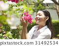 a portrait of young lady holding bougainvillaea branch outdoors 31492534
