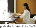 a smiling woman is writing email on the laptop. 31492628