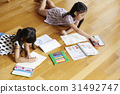 Two little girls are lying on the floor and drawing on paper. 31492747