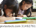 The kids are studying at home with pencils. 31492761