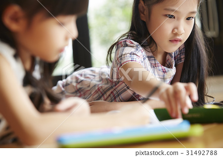 little girl is studying next to another girl at home. 31492788