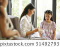 Daughter is eating breakfast with her mother. 31492793