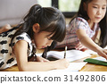 Two little girls are drawing by color pencils 31492806