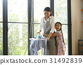 mom irons clothes, receives a warm hug from a happy daughter 31492839
