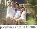 Two little girls and a woman are sitting on a swing and smiling. 31492882