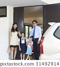 A happy family with two girls is standing at door and beside a car. 31492914