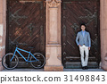 Happy smiling man standing in shadow of building 31498843