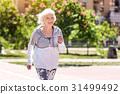 Joyful old pretty woman doing morning exercise 31499492