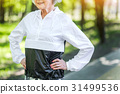 Happy fit senior woman exercising in city park 31499536