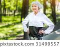 Jolly senior lady training among green trees 31499557
