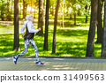 Happy fit old woman running along sidewalk among 31499563