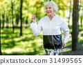 Jolly senior woman enjoying running in forest 31499565