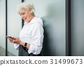 Happy old woman using her smartphone nearby city 31499673