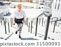 Cheerful aged woman training on steps with guard 31500093
