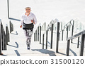 Cheery elderly lady running up concrete steps 31500120