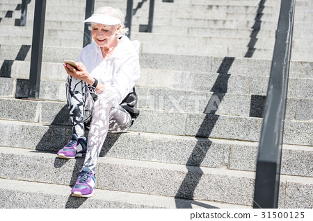 Jolly senior woman texting via mobile phone on 31500125
