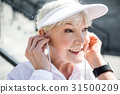 Cheerful senior lady using hands free during 31500209