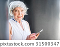 Happy elderly lady using cellphone for 31500347