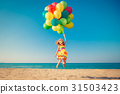 Happy child jumping with colorful balloons on sandy beach 31503423