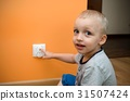 Child near to the electrical socket 31507424