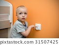 Child near to the electrical socket 31507425