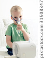 Boy making inhalation with nebulizer at home 31508347