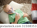 Boy making inhalation with nebulizer at home 31508353