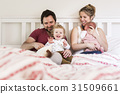 Young parents in bed with their cute little 31509661