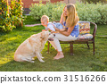 Happy family playing with their dog on a sunny day 31516266
