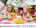 Cute children blowing together on the candle during a birthday party 31525823