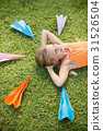Young girl lying on grass around paper planes 31526504