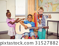 Portrait of smiling kids playing guitar, violin, flute in classroom 31527882