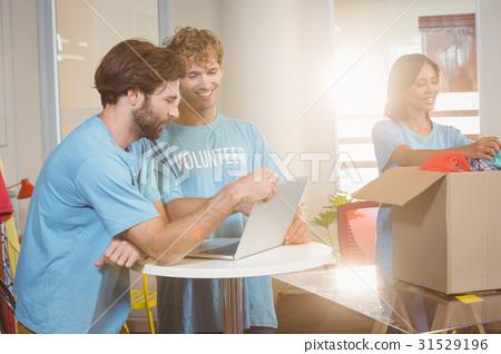 Volunteers using a laptop 31529196