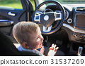 Happy boy sitting on the driver seat in the car 31537269