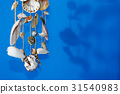 A wind chime with shells on a blue background 31540983