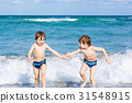 Two kid boys running on ocean beach in Florida 31548915