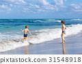 Two kid boys running on ocean beach in Florida 31548918